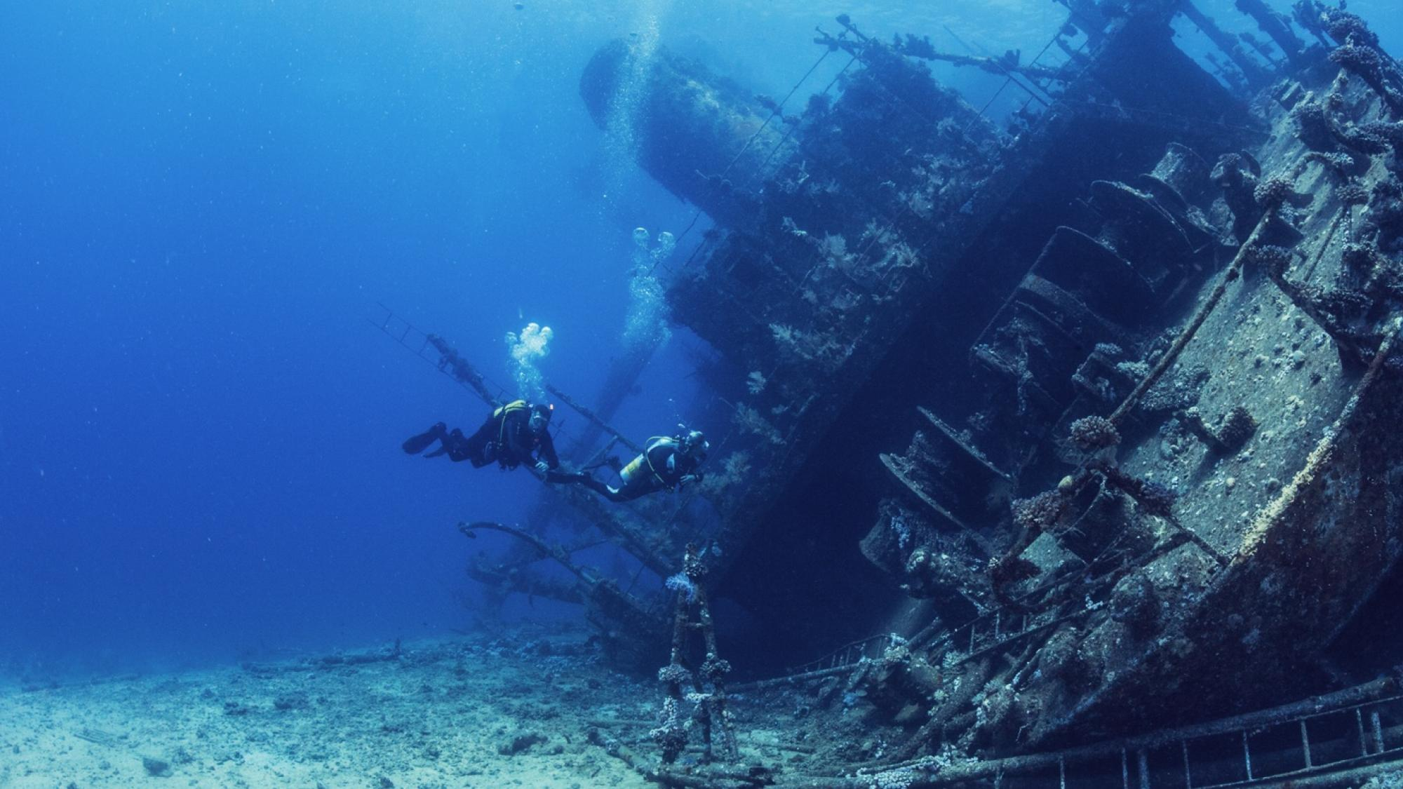 advanced open water diver swimming next to large sunken ship