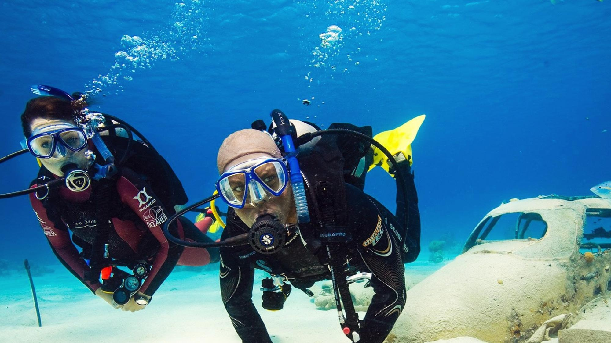 man and woman SCUBA diving looking at the camera