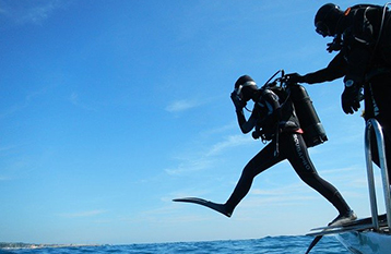SCUBA Diver jumping into water